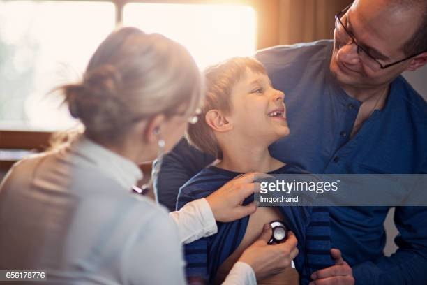 father with son having medical examination - visita imagens e fotografias de stock
