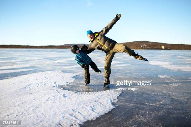 father with son ice-skating on frozen lake - swedish lapland stock photos and pictures