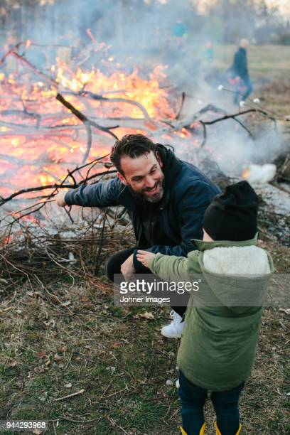 father with son looking at fire in park - noite de walpurgis imagens e fotografias de stock