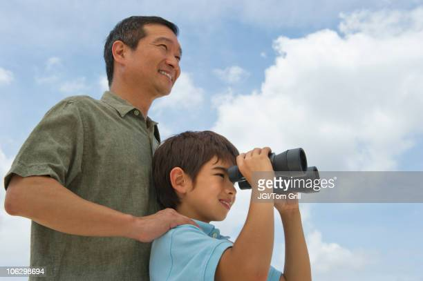 Father with son looking through binoculars