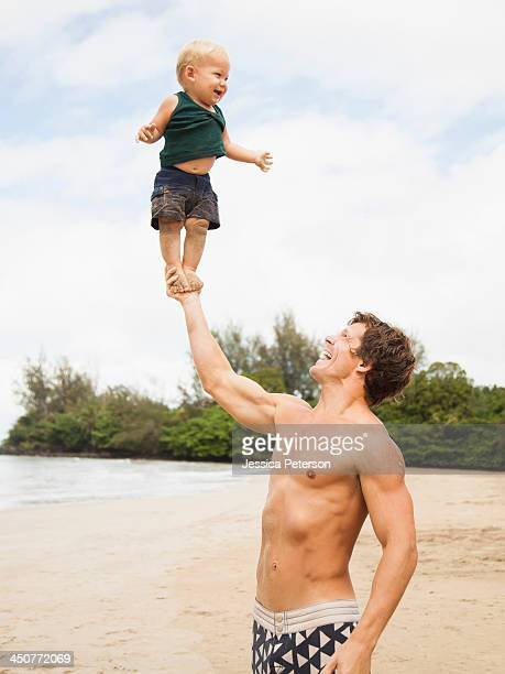 father with son (6-11 months) on beach - bare breasted babes stock pictures, royalty-free photos & images