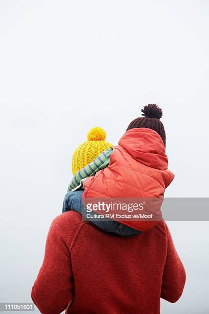 Father with son on shoulders in winter