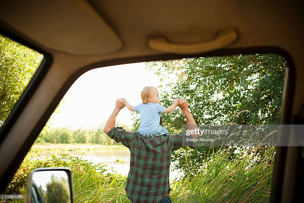 Father with son on shoulders, viewed from a car : Stock Photo