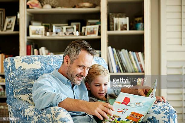 Father with son reading story book at home