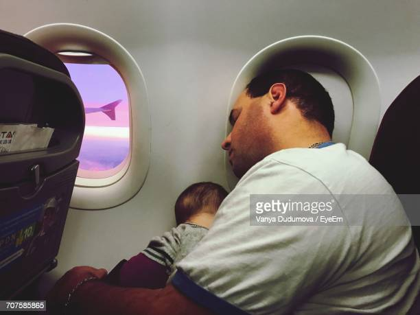 Father With Son Sleeping In Airplane During Sunset