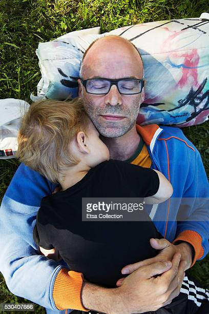 Father with son sleeping on grass