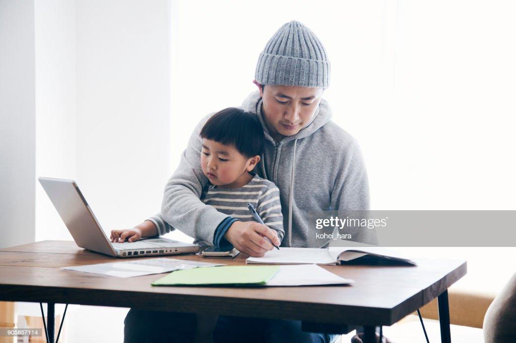 Pai com filho, trabalhando em casa : Foto de stock