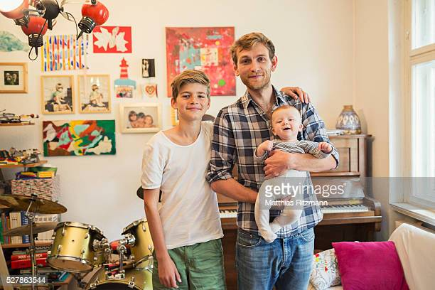 father with sons (12-23 months, 13-15) in living room - 12 23 months stock pictures, royalty-free photos & images