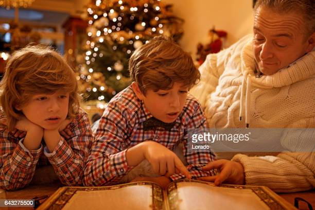 Father with sons reading a book in christmas scene with festive decorations in indoor setting