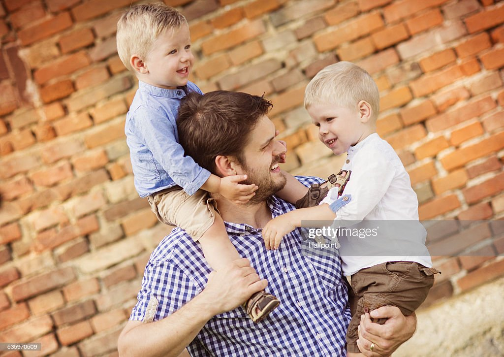 Father with sons relaxing together in nature : Stock Photo