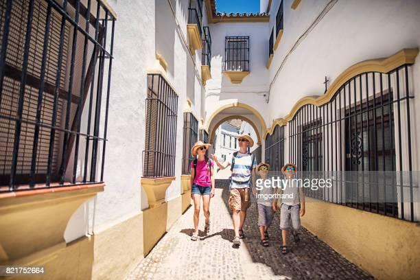 padre con tres hijos caminando por calles de ronda, españa - ronda fotografías e imágenes de stock