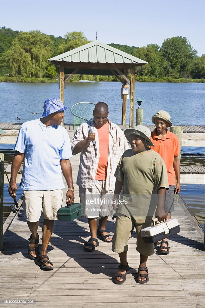 Father with three sons (11-14) walking on jetty with fishing equipment : Foto stock