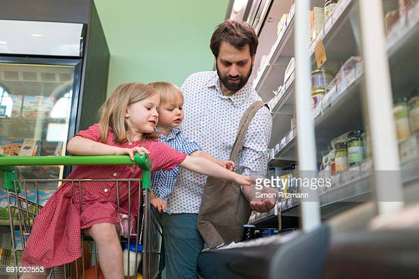 Father with toddler children in grocery store