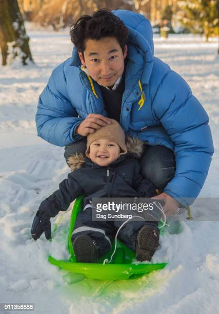Father with toddler on green baby sled