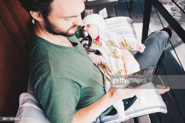 Father with toddler using mobile phone while sitting on chair at holiday villa