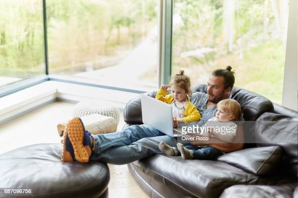 Father with two children looking at laptop on the couch