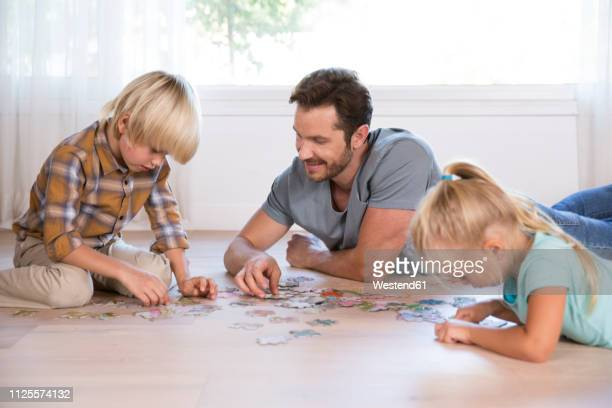 father with two children lying on the floor at home playing jigsaw puzzle - puzzle stock-fotos und bilder