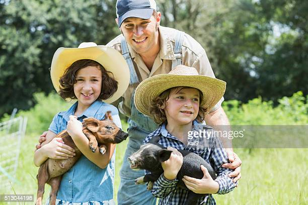 Father with two children on family farm holding pigs
