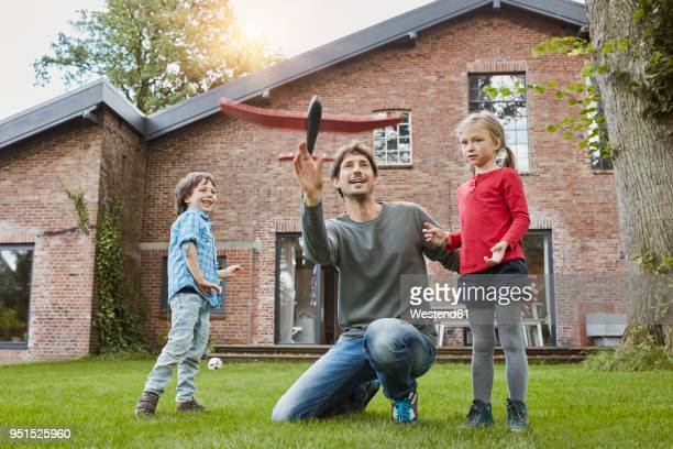 father with two children playing with toy airplane in garden of their home - middle class stock pictures, royalty-free photos & images