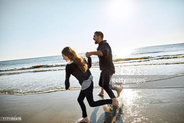 father with two children running at the sea - pre adolescent child stock pictures, royalty-free photos & images
