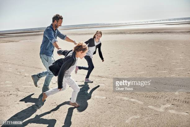 father with two children running on the beach - pre adolescent child stock pictures, royalty-free photos & images