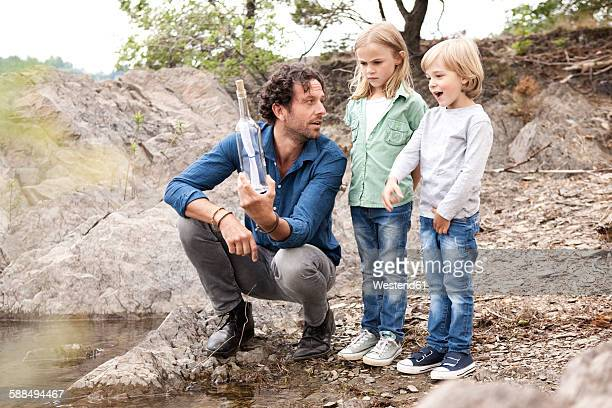 Father with two children with message in a bottle at lakeshore