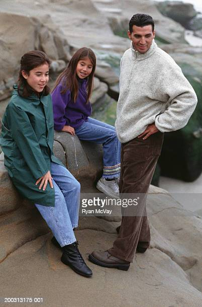 father with two daughters  (8-9), (12-13), resting on rocks at seashore - fleecejas stockfoto's en -beelden