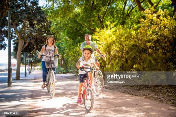 father with two daughters riding bike in valencia - valencia spain stock pictures, royalty-free photos & images