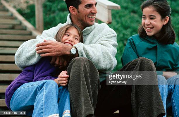 father with two daughters (8-9), (12-13), sitting on wooden steps, outdoors - fleecejas stockfoto's en -beelden