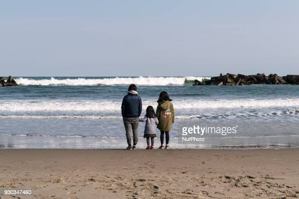 A father with two daughters stands there silently on Arahama beach after a moment of silence at 246 pm at Wakabayashi Ward Miyagi prefecture at 11...