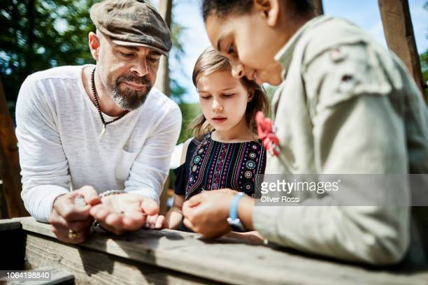 father with two girls at a water feature on a playground - multikulturalismus stock-fotos und bilder