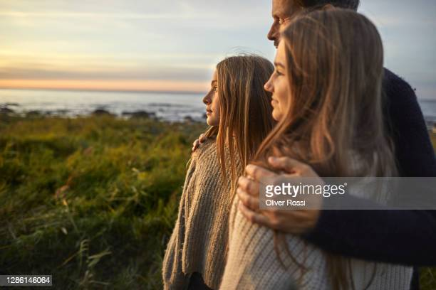 father with two girls looking at view at the sea - parenting stock pictures, royalty-free photos & images