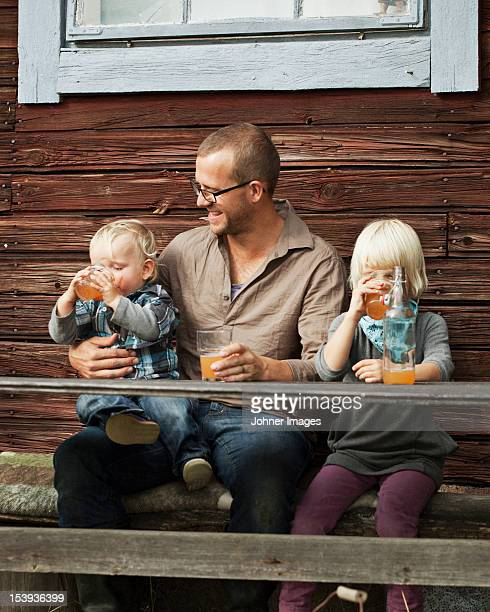 father with two kids drinking juice in front of wooden house - cider stock pictures, royalty-free photos & images