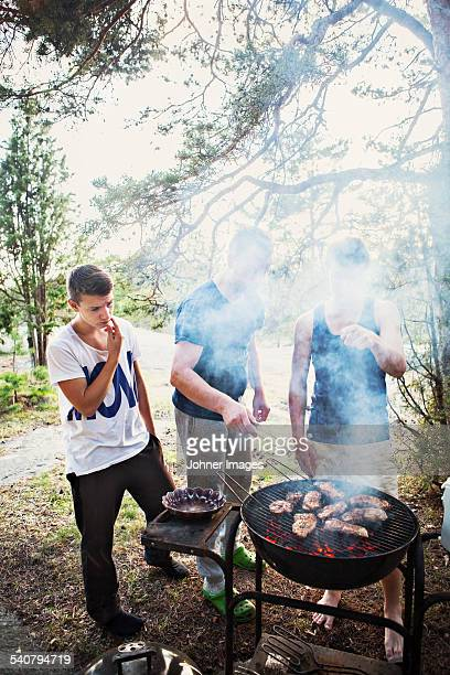 Father with two sons having barbecue