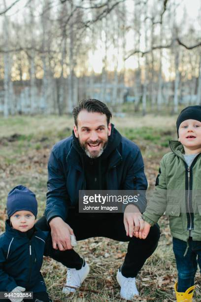father with two sons playing in park - noite de walpurgis imagens e fotografias de stock