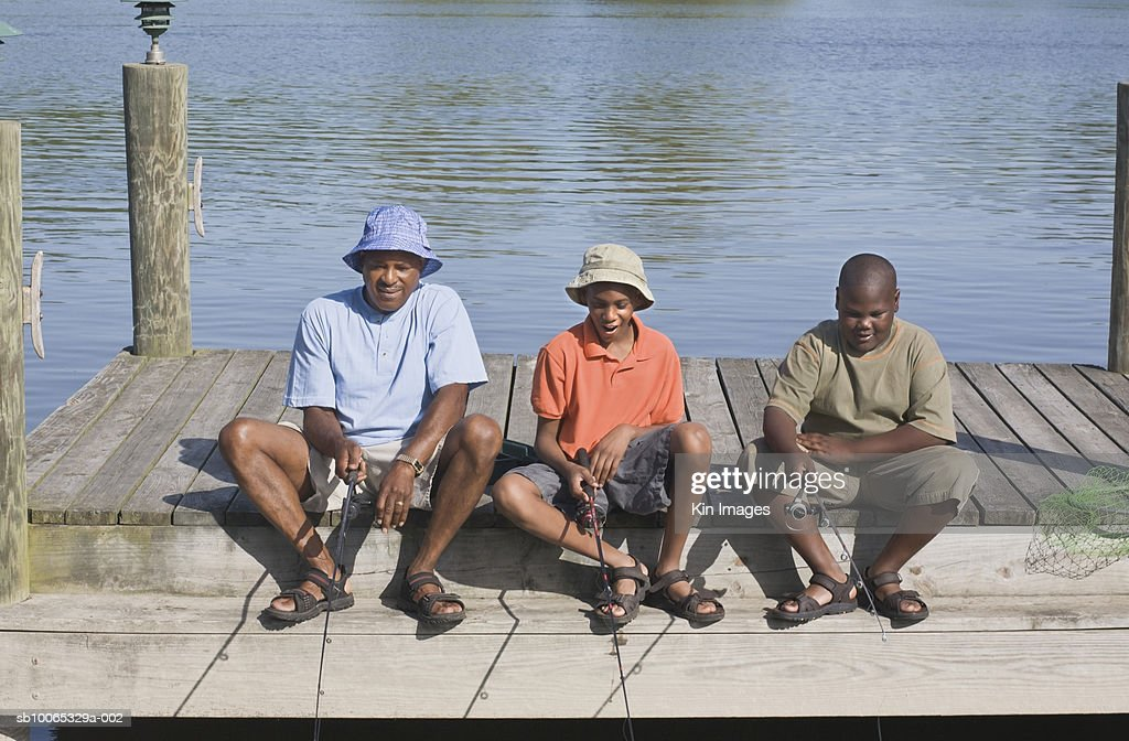 Father with two sons (11-13) sitting on jetty with fishing rods : Foto stock