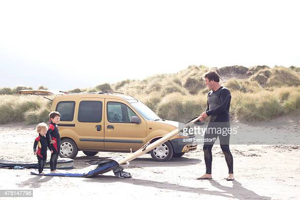 Father with two sons, surfboard and car on beach