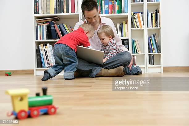 Father with two sons trying to using a mobile phone and a laptop