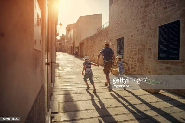 father with two sons visiting mediterranean town. - city break stock pictures, royalty-free photos & images