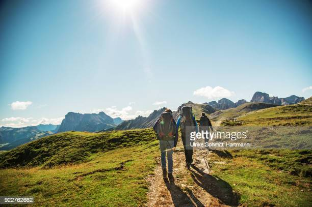 Father with two teenage children hiking in the Alps