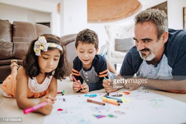 pai com dois miúdos novos que desenham e que têm o divertimento. - latino americano - fotografias e filmes do acervo