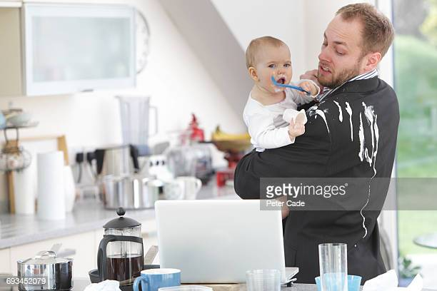 Father with yogurt spilled on suit by baby