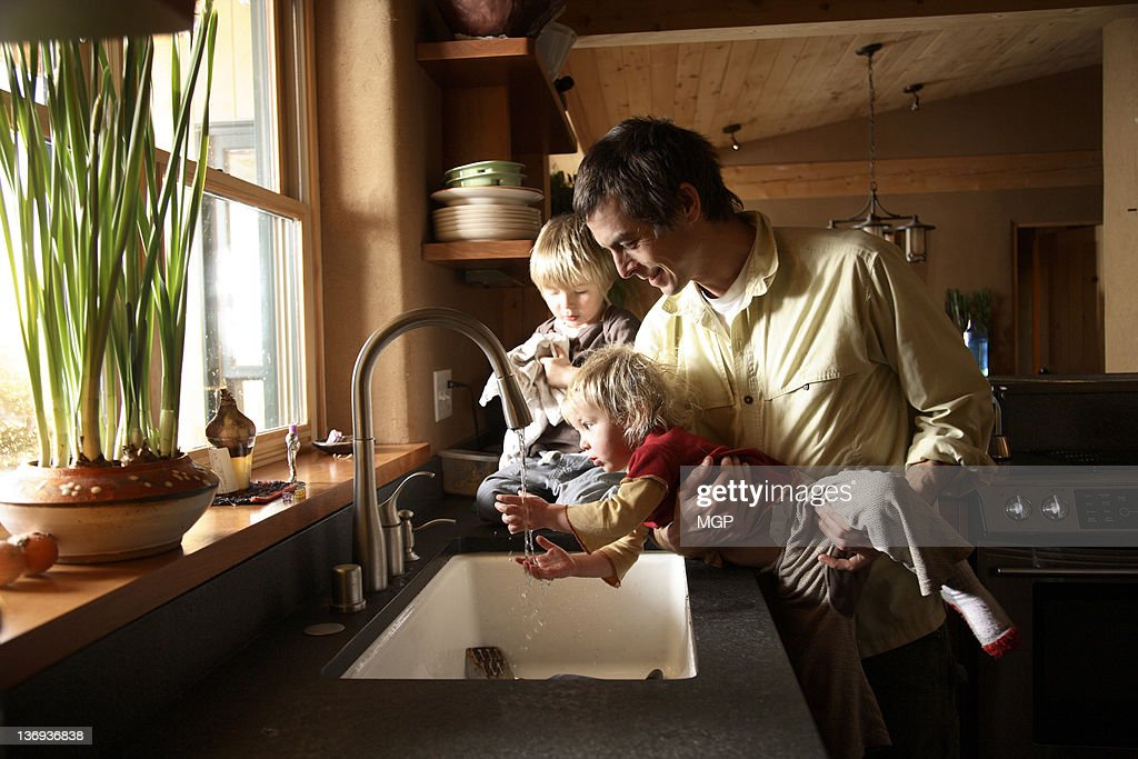 Father with young children at sink : Stockfoto