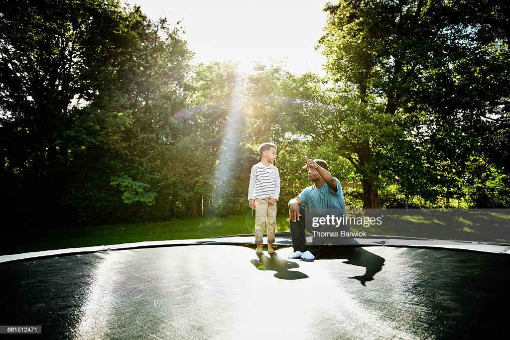 Father with young son on trampoline : Stock Photo