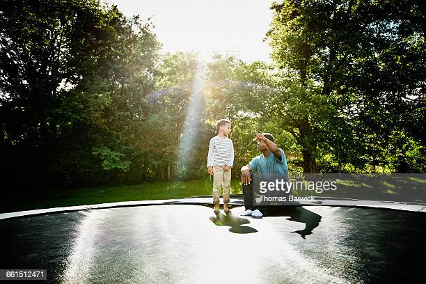 Father with young son on trampoline