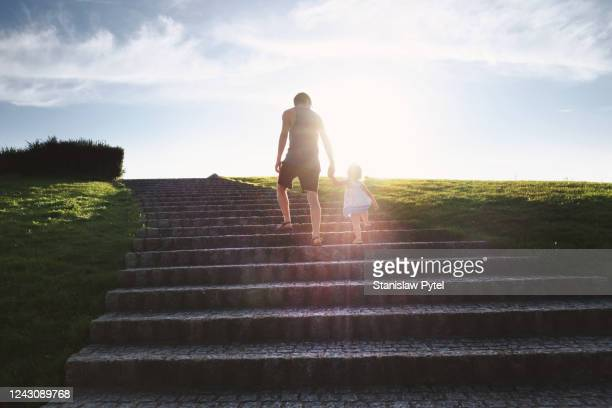 father wlaking with  daughter by hand on big stairs in park at susnet - genderblend stock pictures, royalty-free photos & images