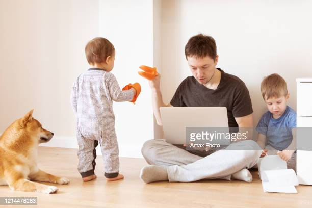 father working at home office while the kids are playing. home office and telecommuting concept - stress coronavirus stock pictures, royalty-free photos & images