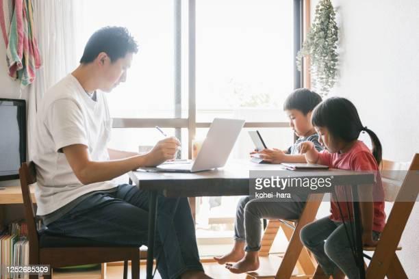 子供と一緒に家で働く父 - テレワーク ストックフォトと画像