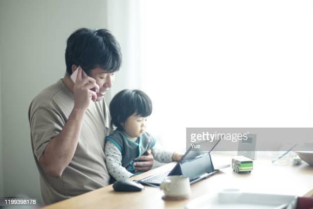 息子と一緒に家で働く父 - テレワーク ストックフォトと画像