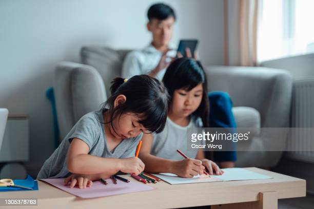 father working from home and helping two daughters with homework - hong kong stock pictures, royalty-free photos & images